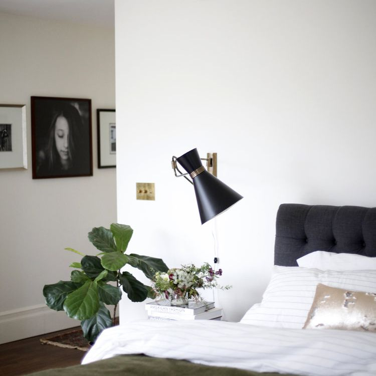 A bedroom with a sleek modern sconce