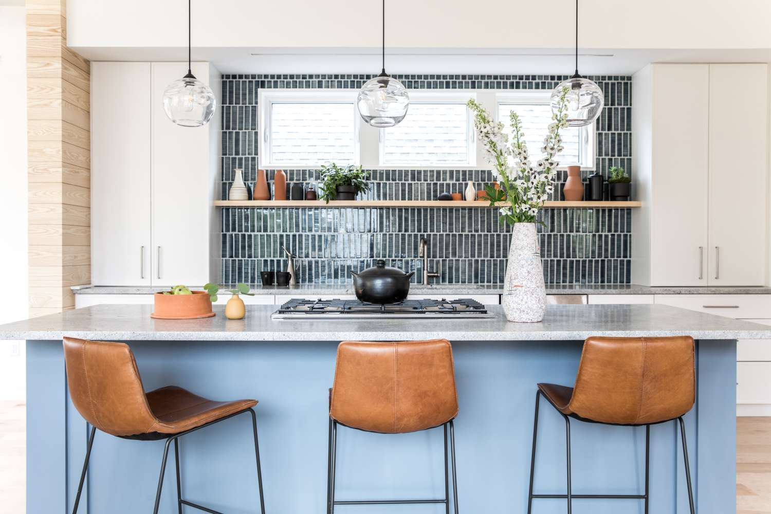 A kitchen with a black tiled backsplash and a light blue painted island