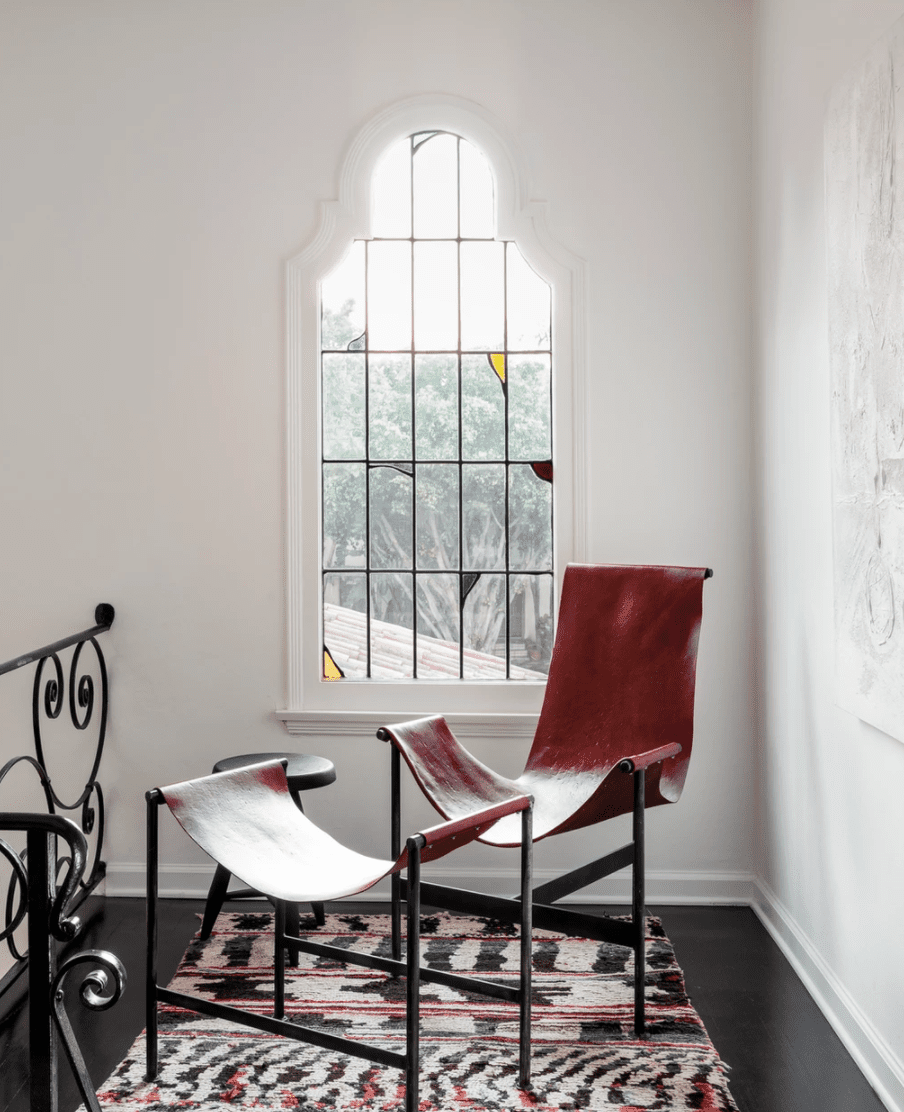 A wall with a stained glass window, behind a red accent chair