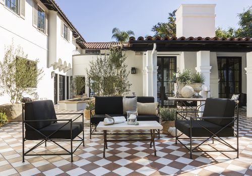 Outdoor living space with large black chairs and sofa.