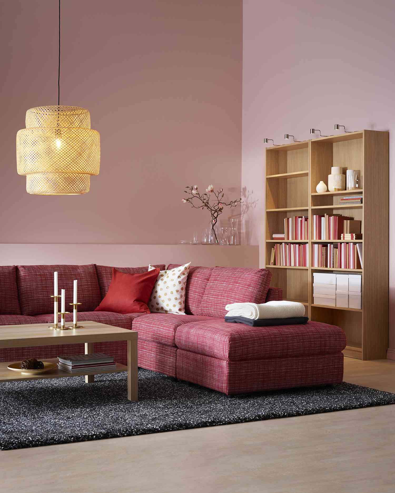 Pink living room with red sectional sofa and warm wood bookcases