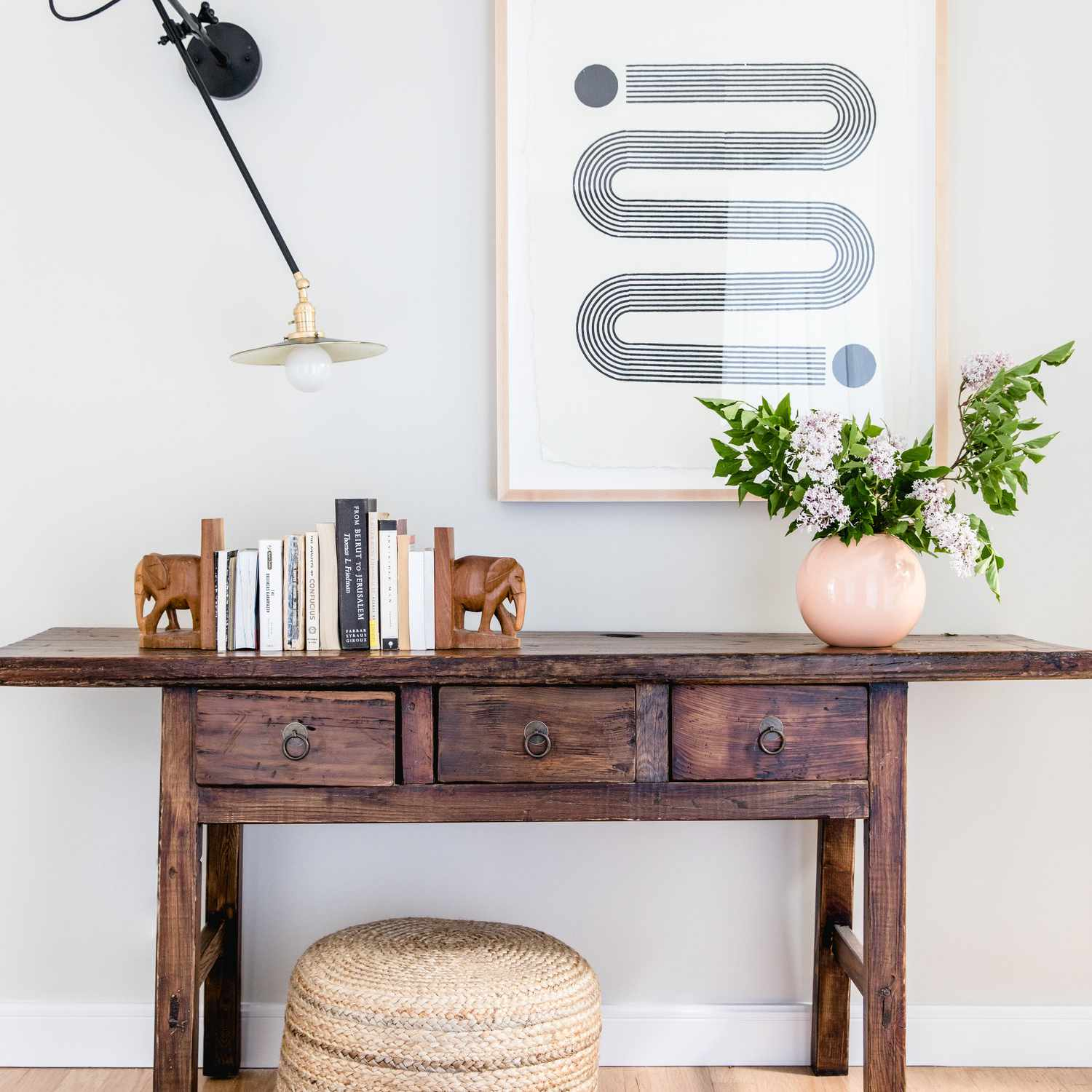 Wooden console with books and plant.