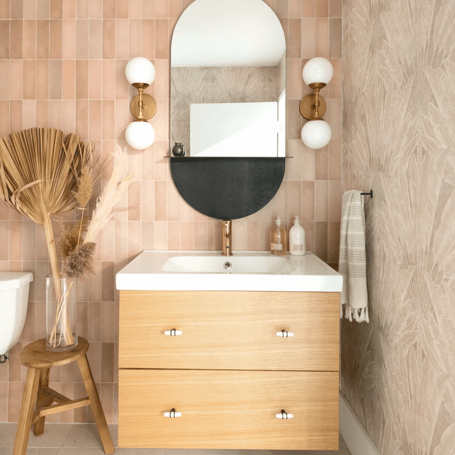 A small half-bathroom lined with two kinds of peach wallpaper