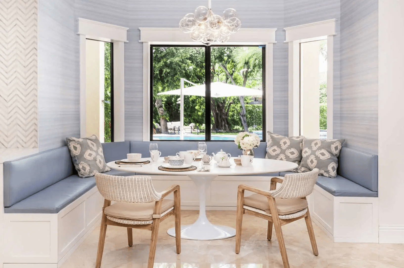 A dining room with a light blue banquette and matching light blue walls