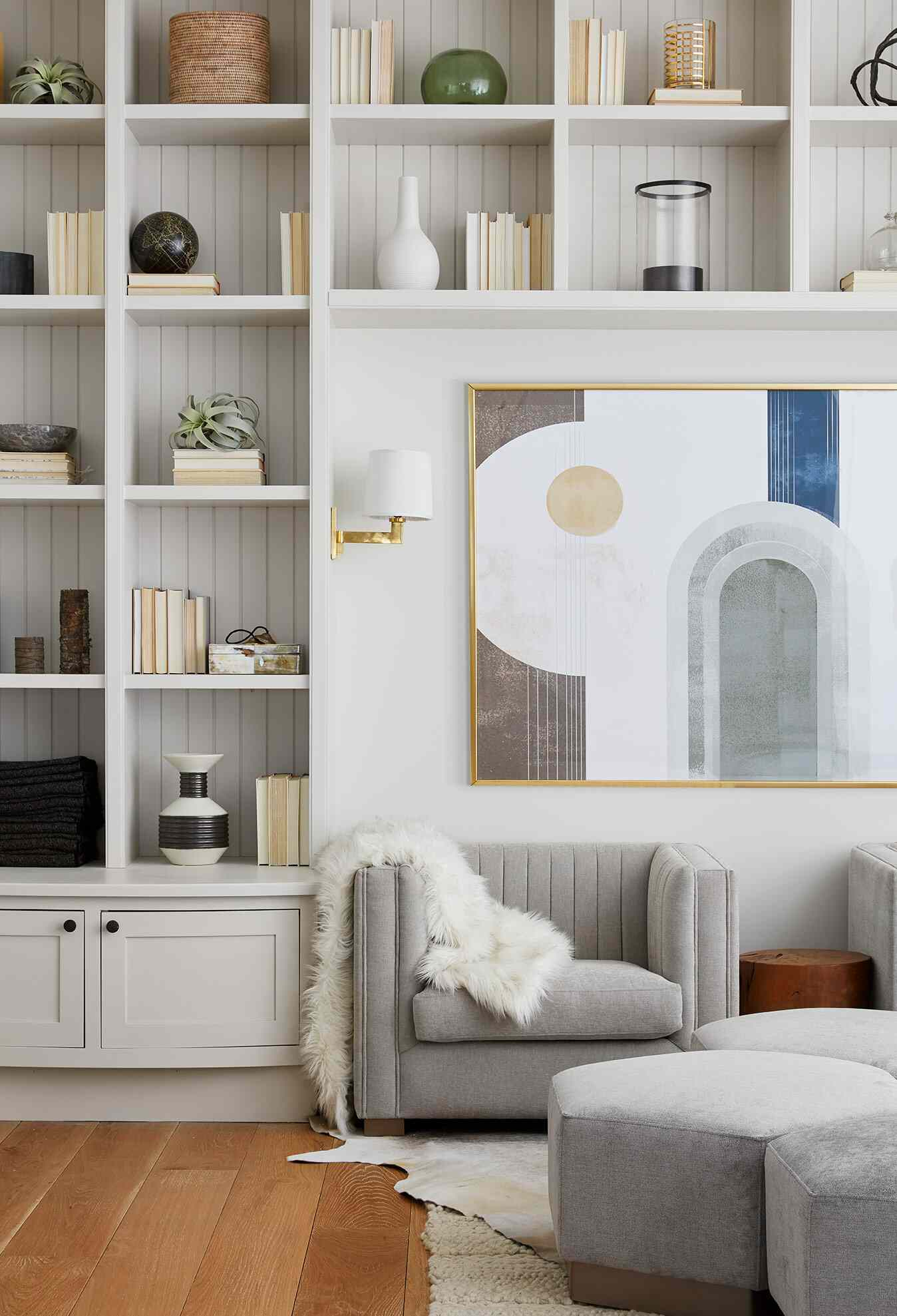 A living room with white bookshelf-lined walls that have been adorned with books and baubles
