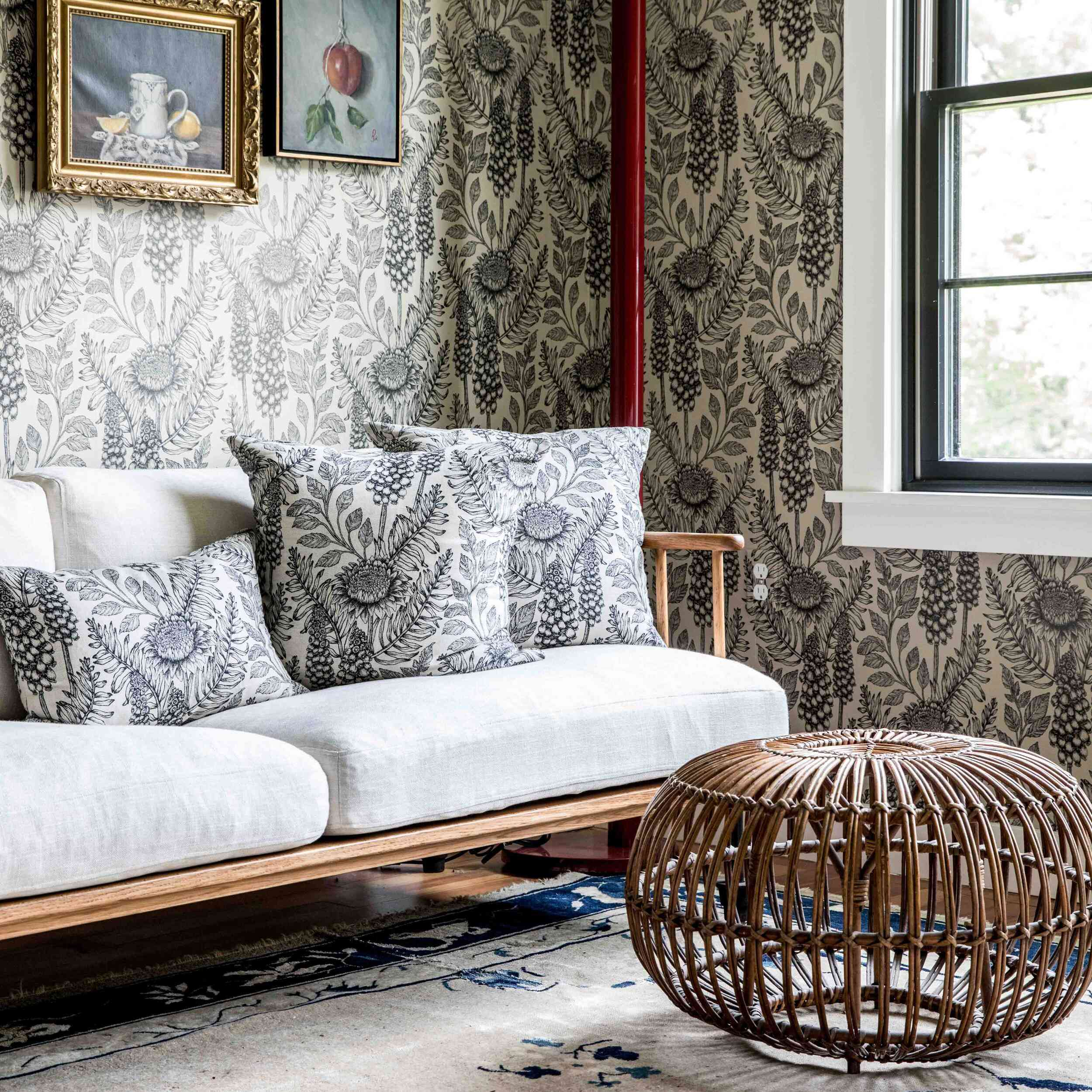 A living room with bold printed wallpaper and matching printed pillows