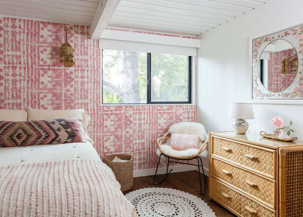 Teen bedroom with pink patterned wallpaper accent wall.