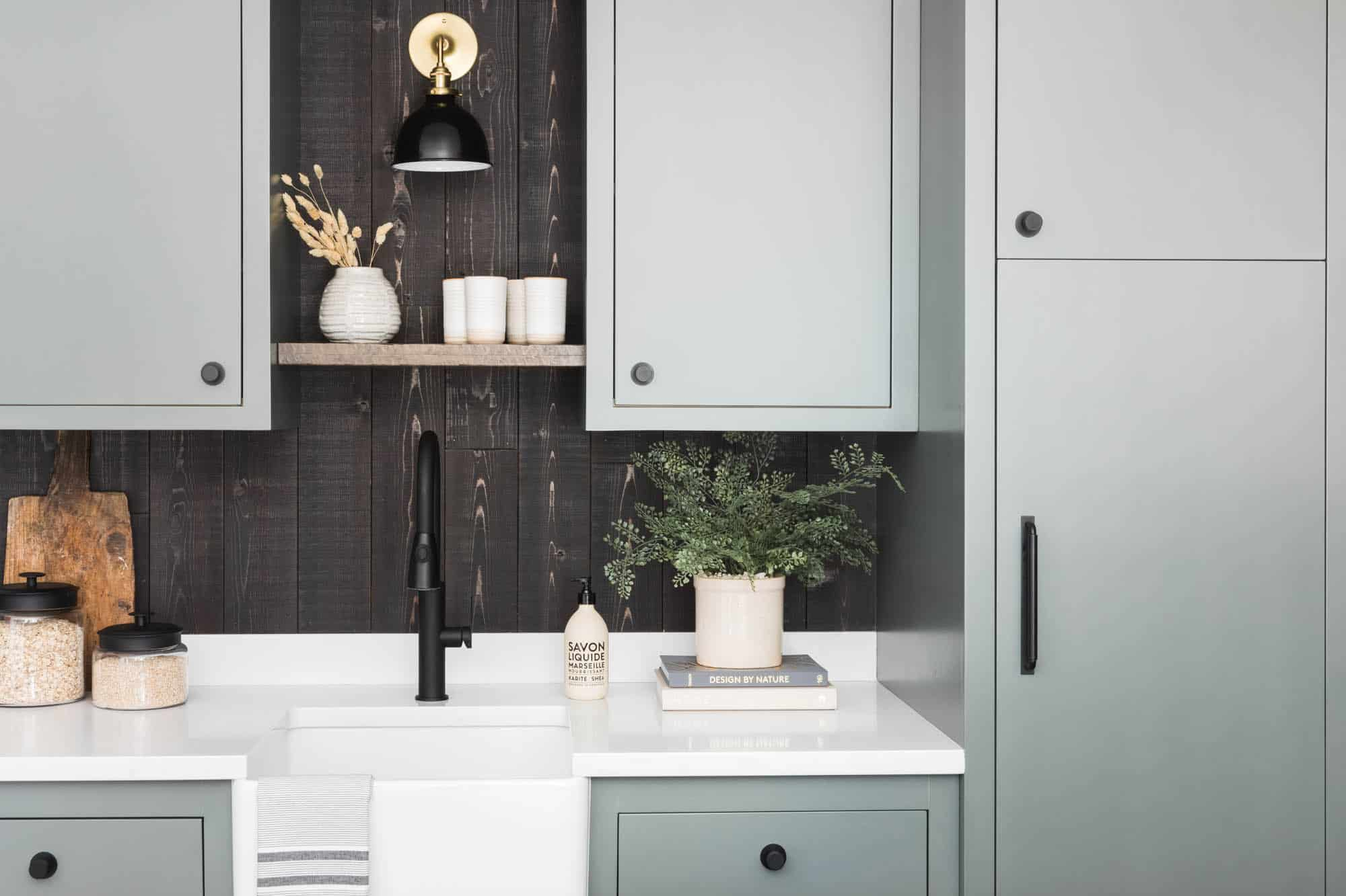 A kitchen with sage green cabinets and a backsplash lined with black wood panels