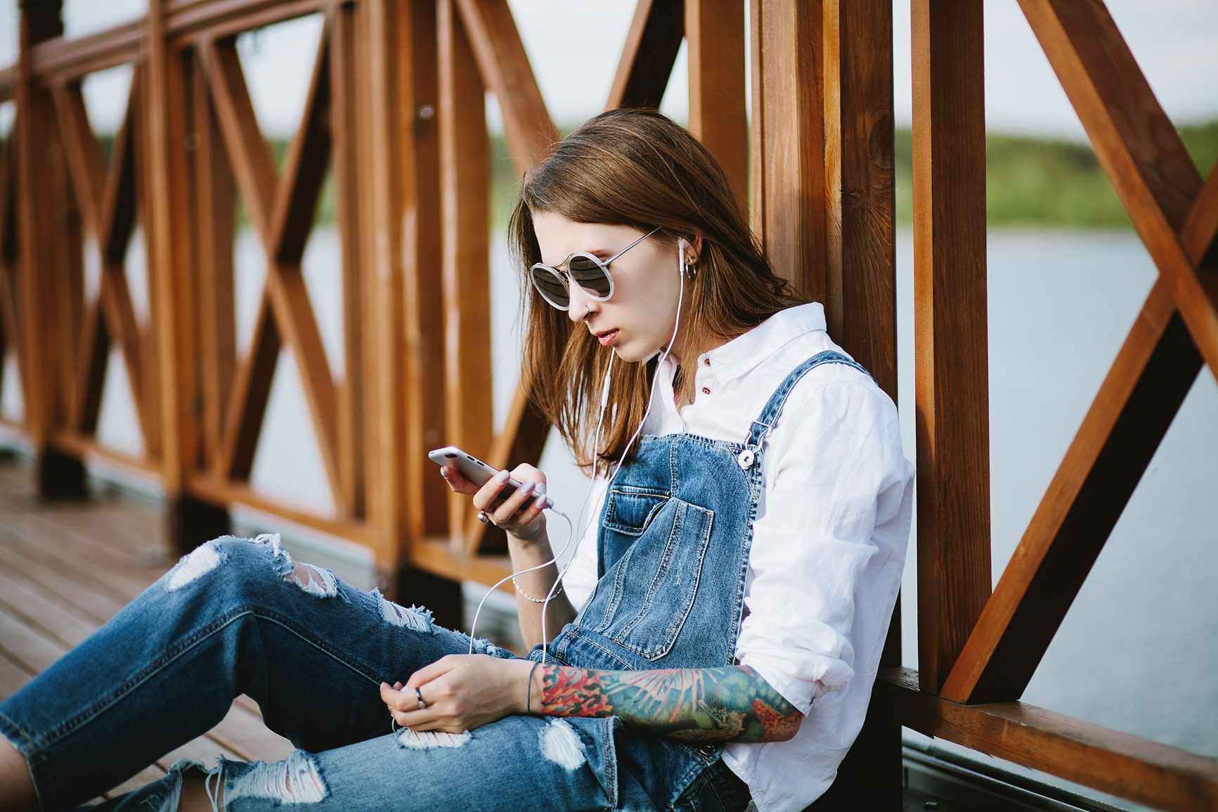 woman sitting on bridge scrolling on phone.