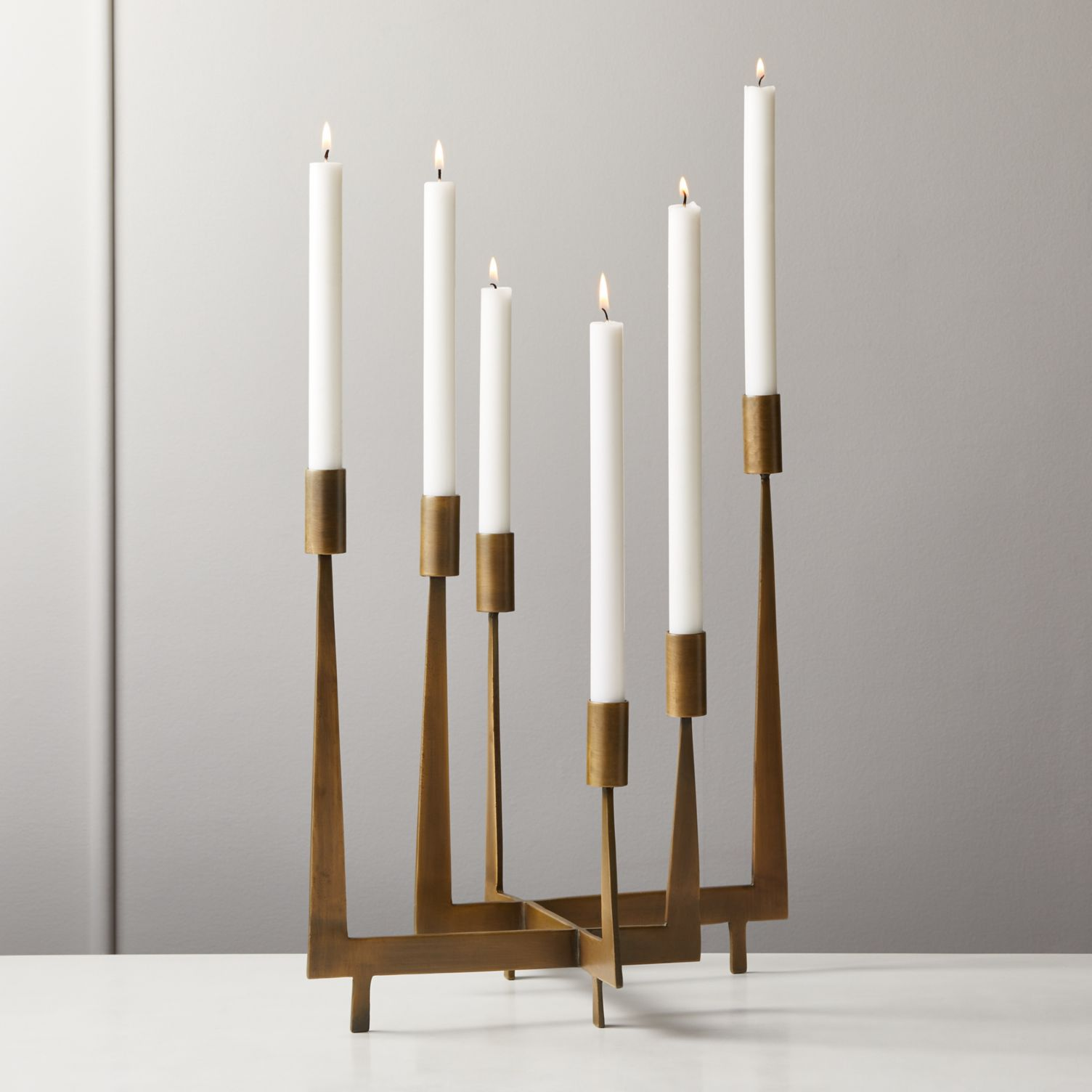 A modern brass candelabra that holds 6 taper candles by CB2.