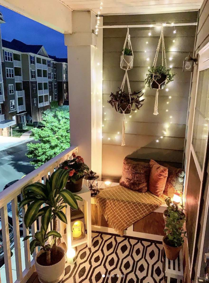 balcony with string lights and hanging plants, nook with pillows and blanket