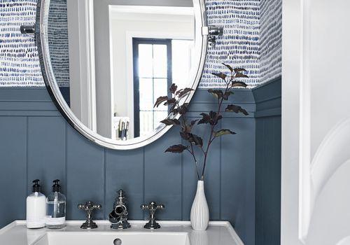 bathroom with blue wood panelling and blue wallpaper