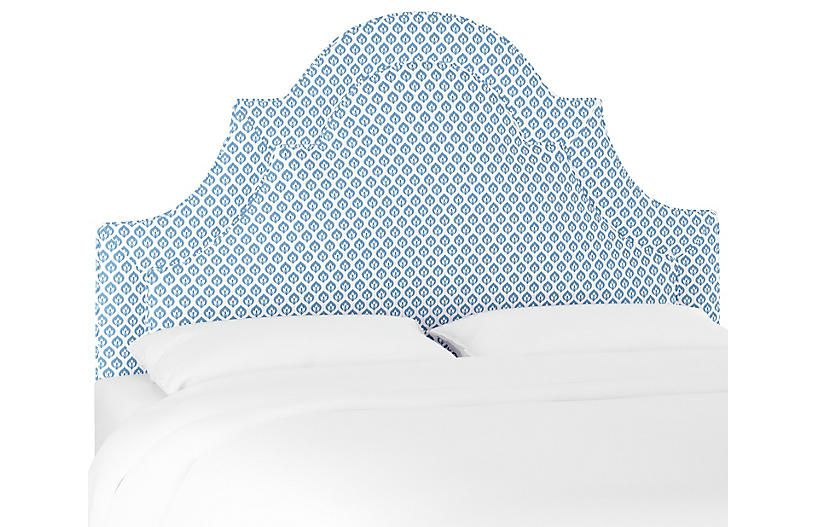 A blue and white upholstered arched headboard.