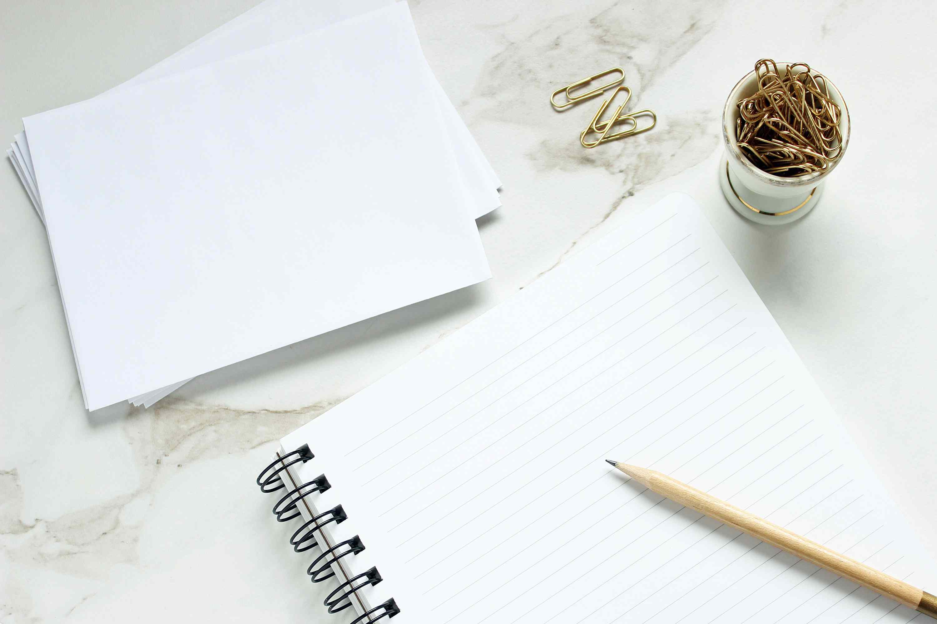 Stationery on marble countertop and gold paperclips
