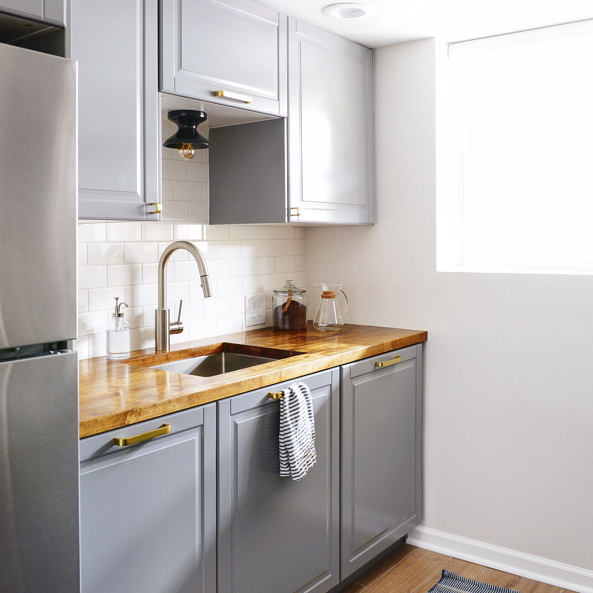 A kitchenette with gray IKEA cabinets