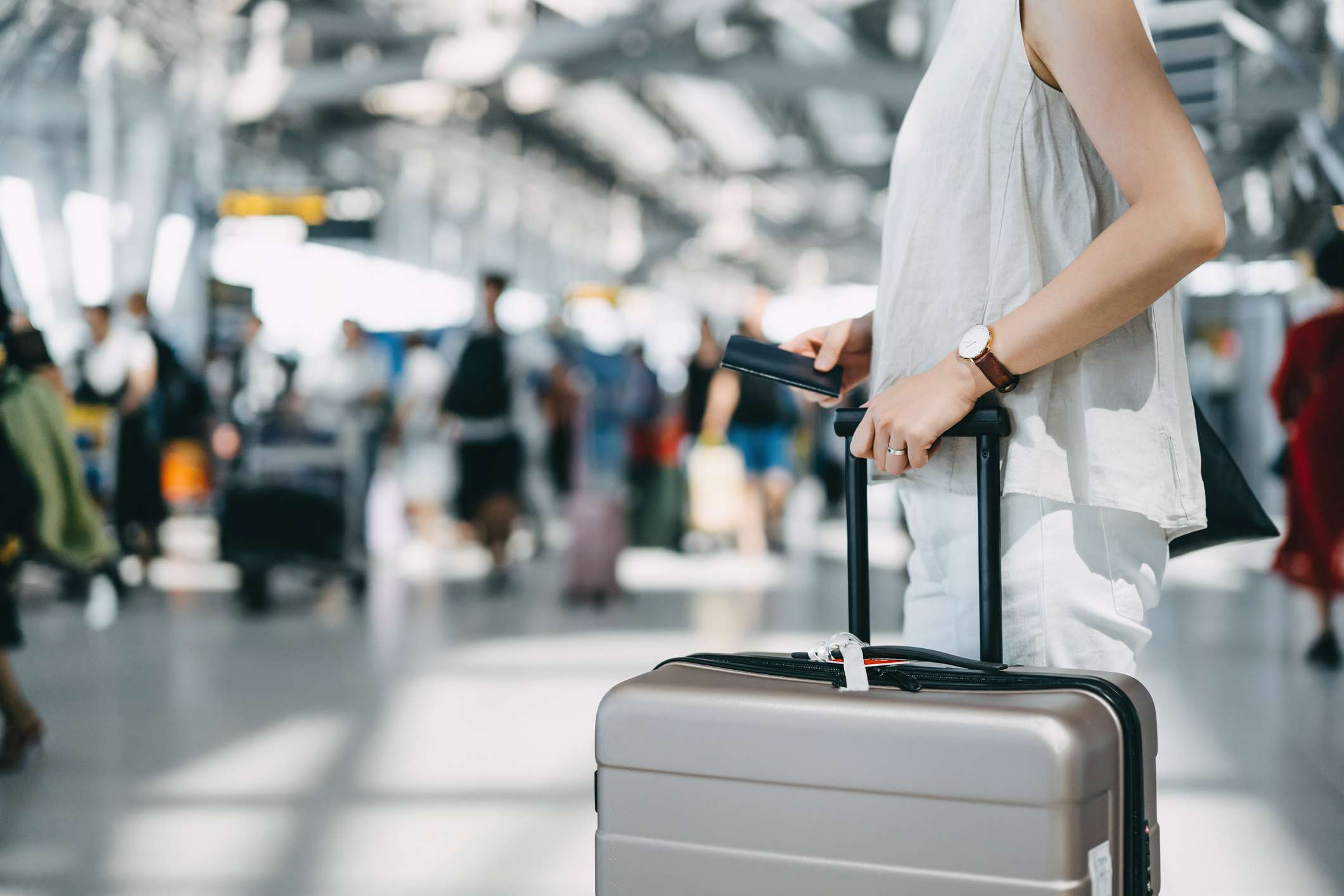 Cropped image of young woman holding passport and suitcase walking in the international airport hall