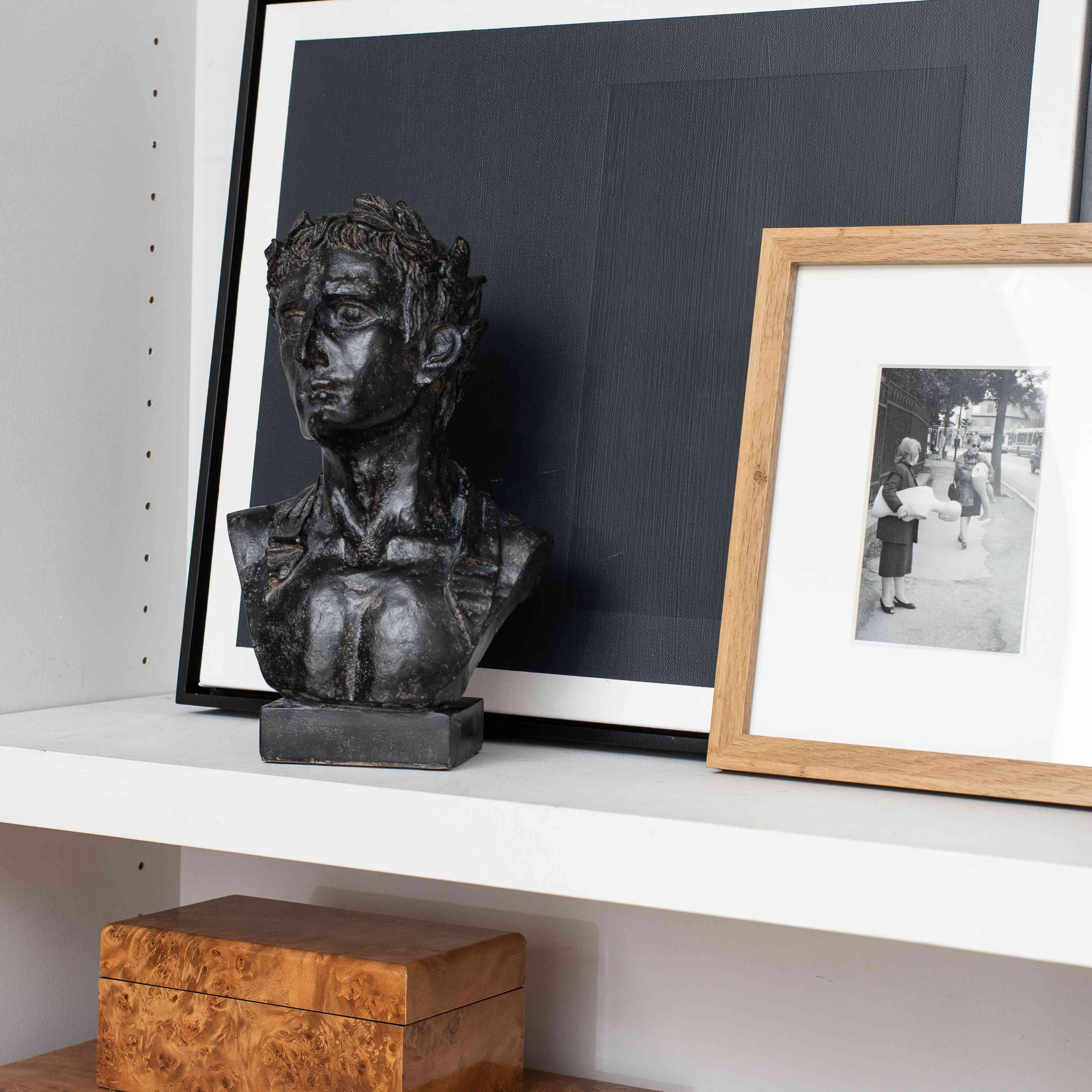 Shelf with bust and artwork.