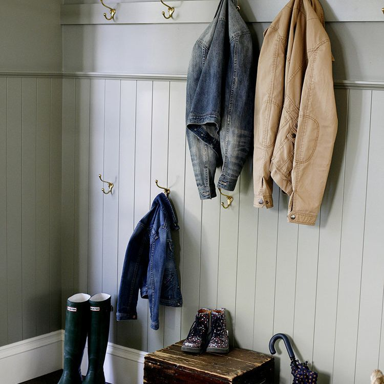 A sage mudroom with several hangers and antique pieces