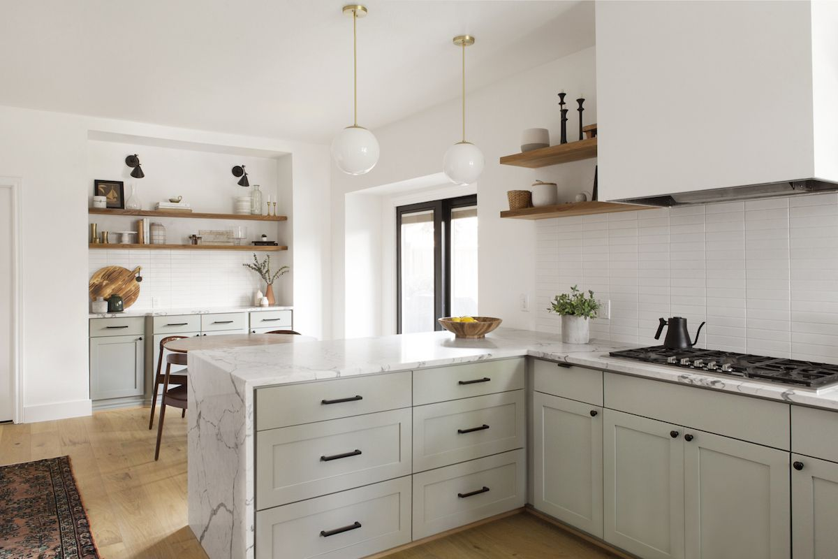 A kitchen with mint cabinets and marble countertops