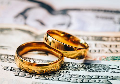 A larger and smaller wedding ring on $20 bills.