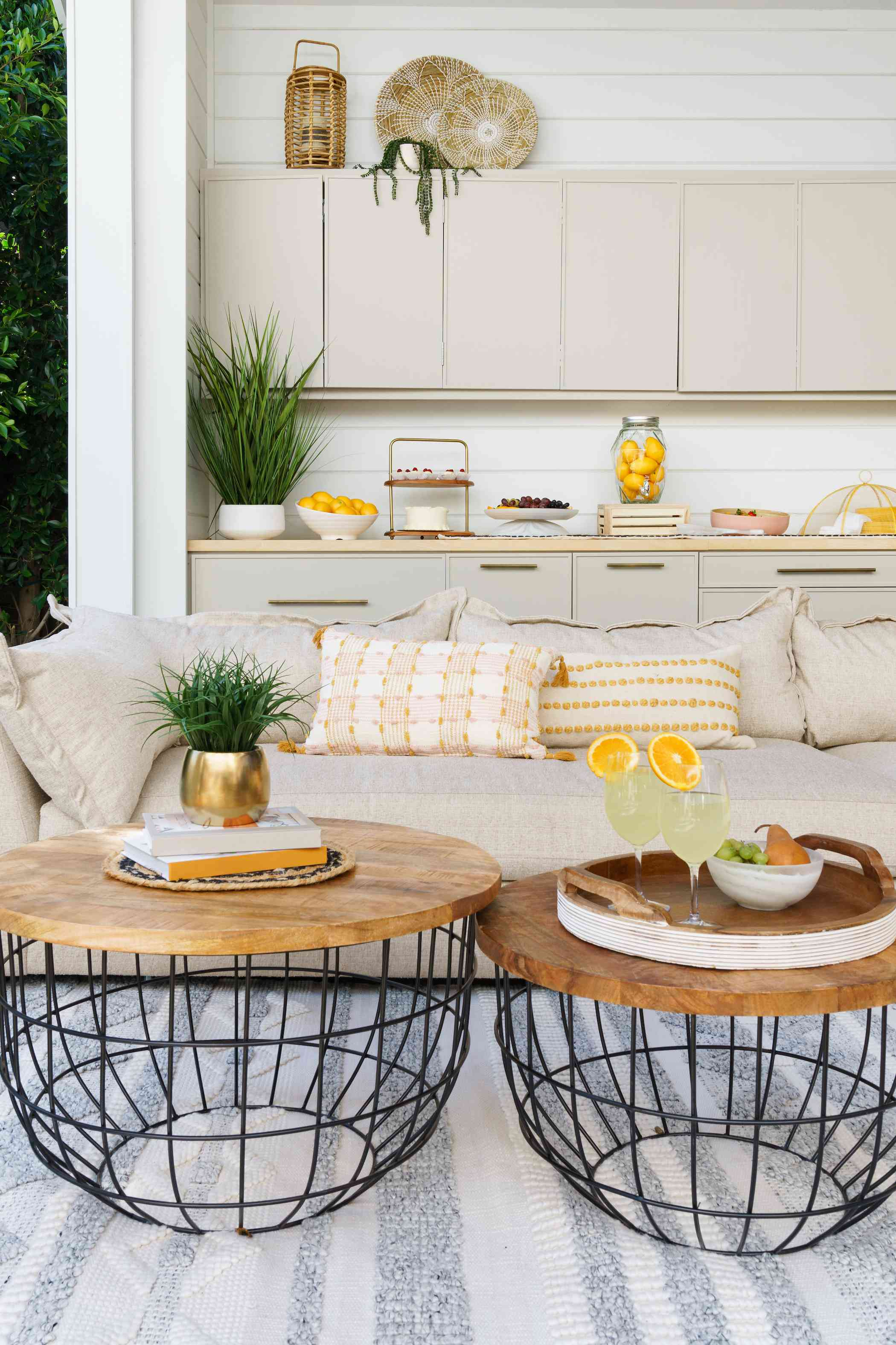 Outdoor space with beige couch and two wood coffee tables.