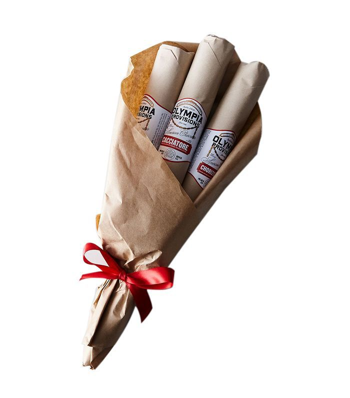 Product shot of Olympia Provisions salami bouquet wrapped in parchment, tied with red ribbon