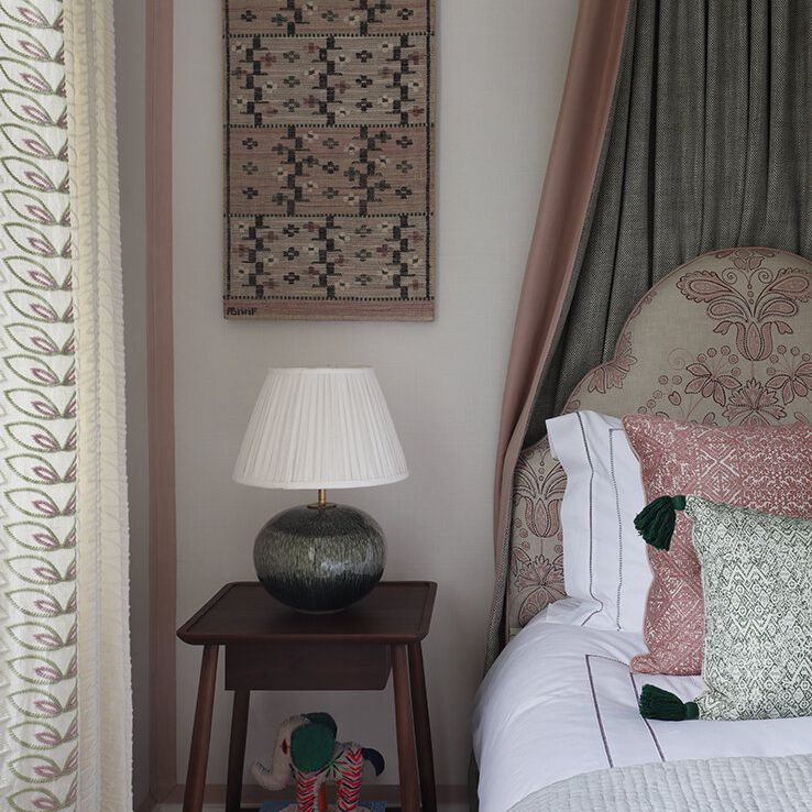 A dark bedroom with a canopy draped behind the headboard