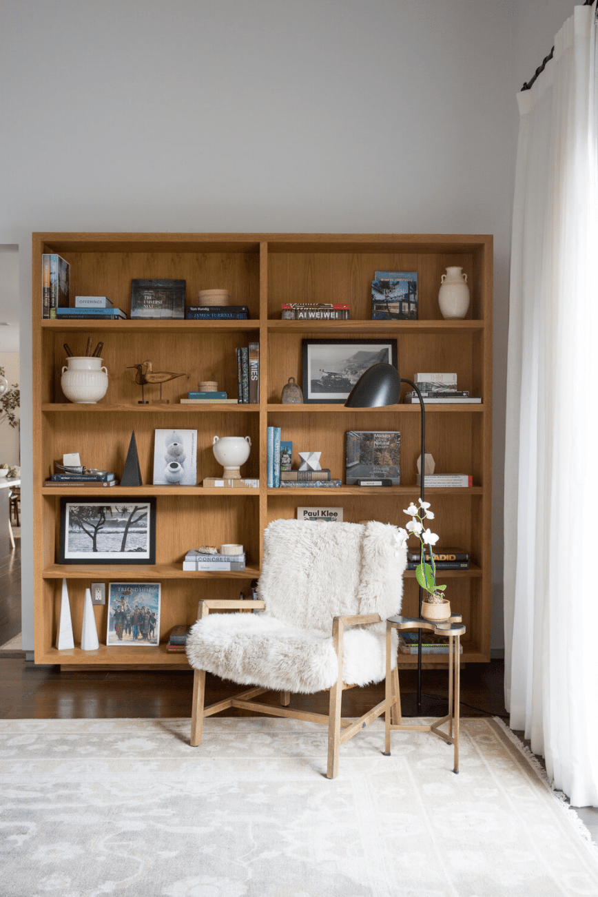 A corner decorated with a wooden bookshelf, a white lounge chair, and a white rug