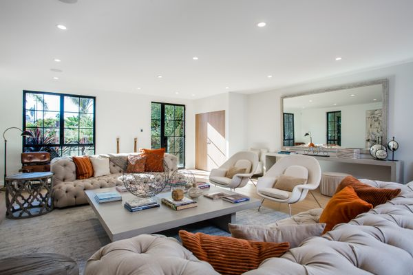 large living room with neutral couches and burnt orange pillows