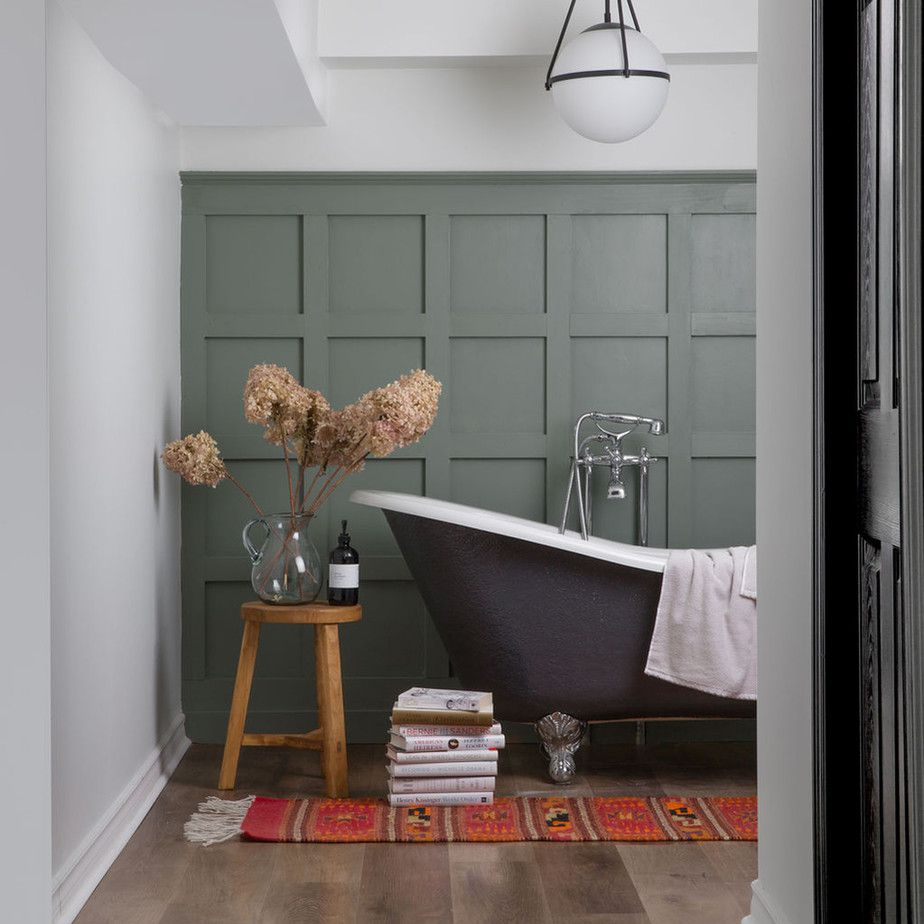 Bathroom with dark wall panelling, dark clawfoot tub, and modern accents