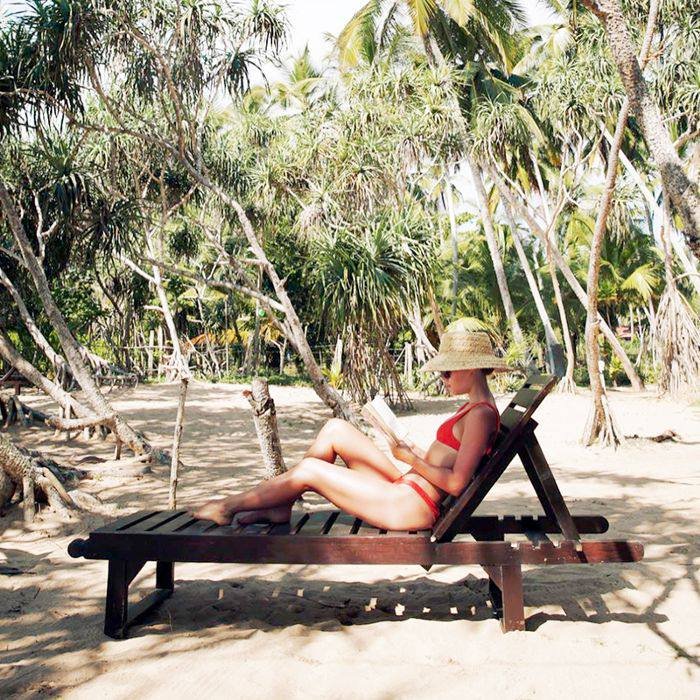 a woman reading on a lounge chair wearing a bikini and straw hat