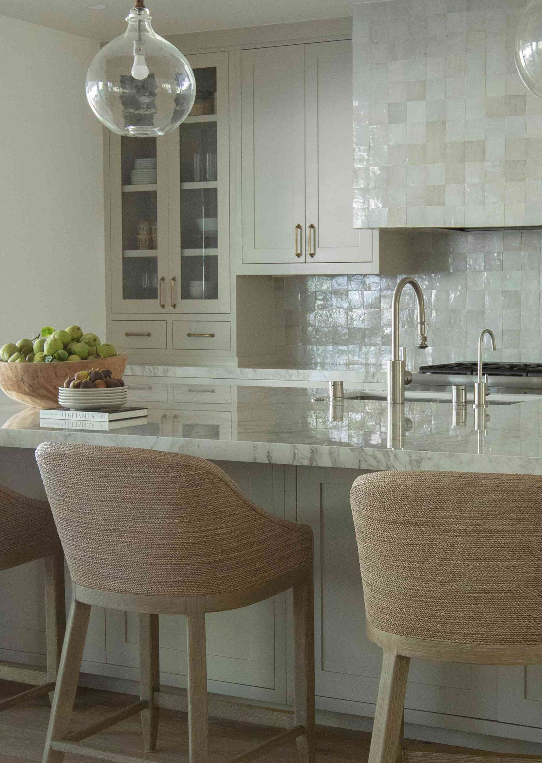 Close up of marble island and jute barstools.