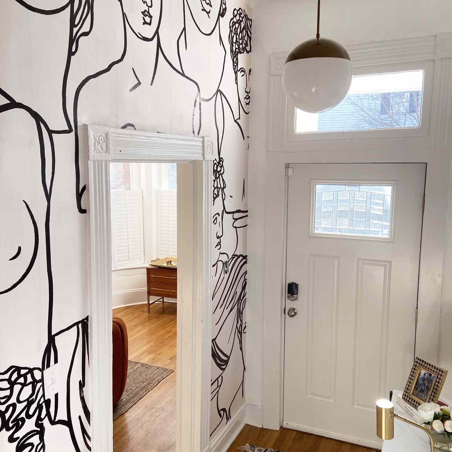 white entryway with murals of faces