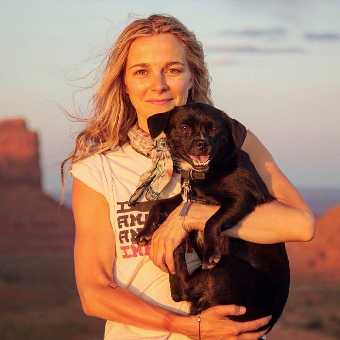 Actress Bojana Novakovic holding a black dog at the Grand Canyon.