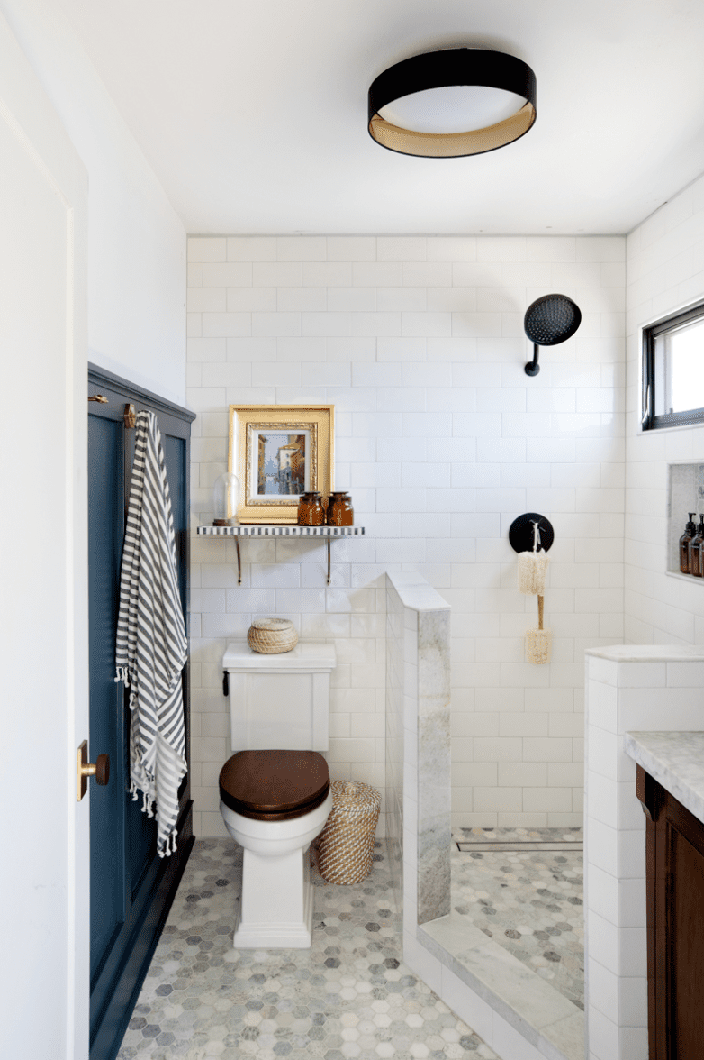 A very small bathroom outfitted with a shower that has waist-high walls