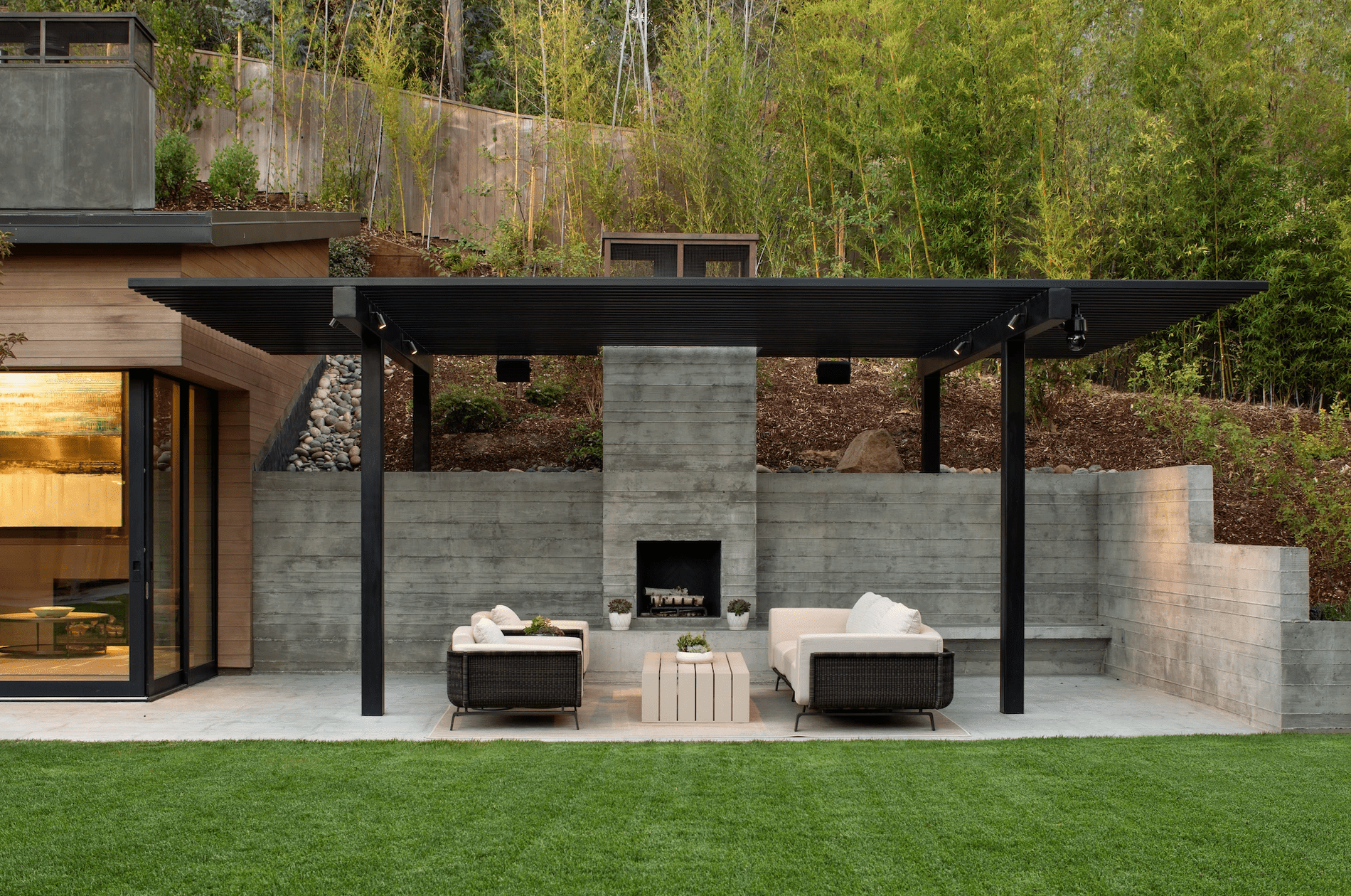 A contemporary outdoor fireplace, paired with a sleek black pergola