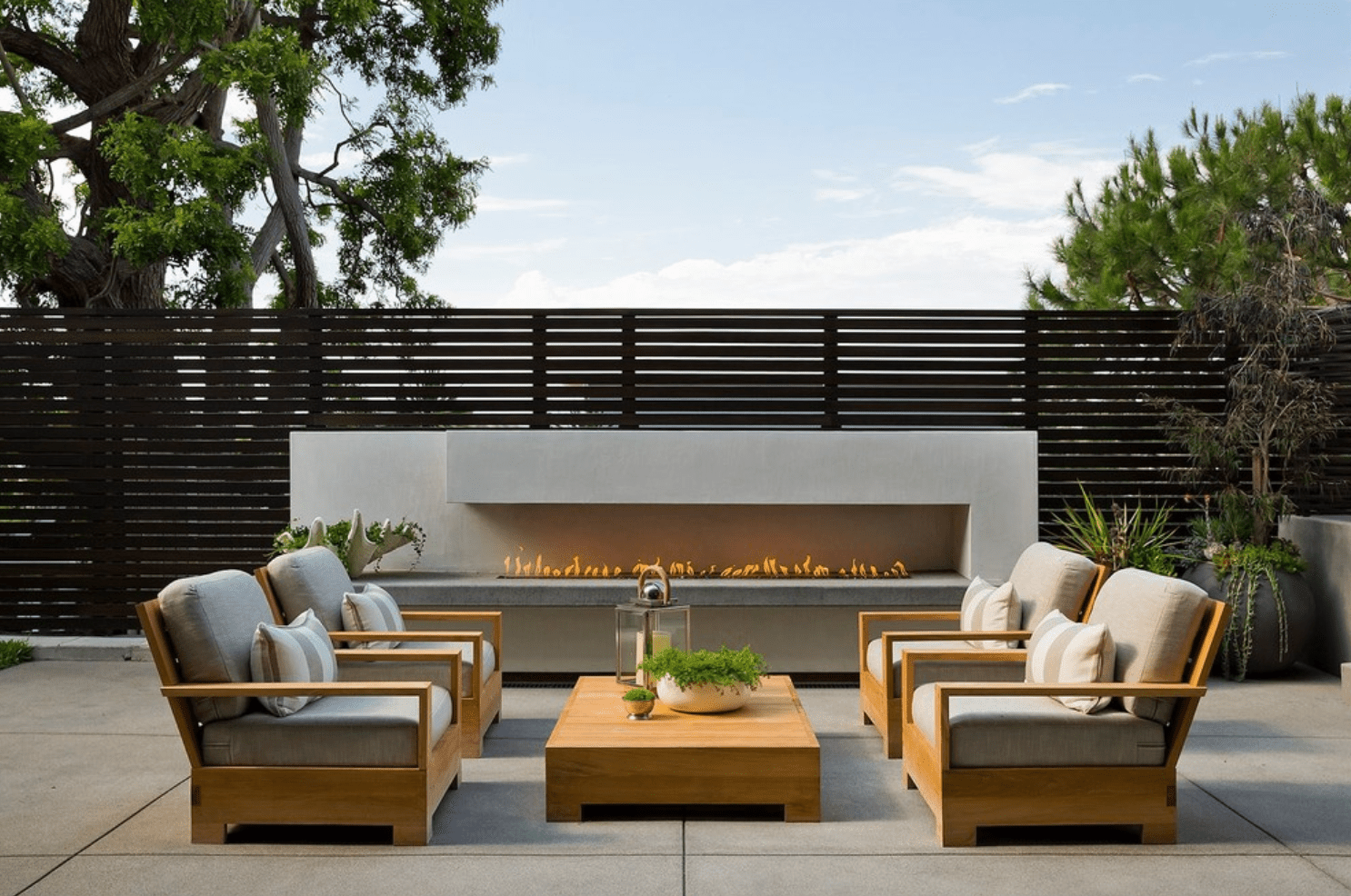 An extremely wide outdoor fireplace, situated near several outdoor lounge chairs