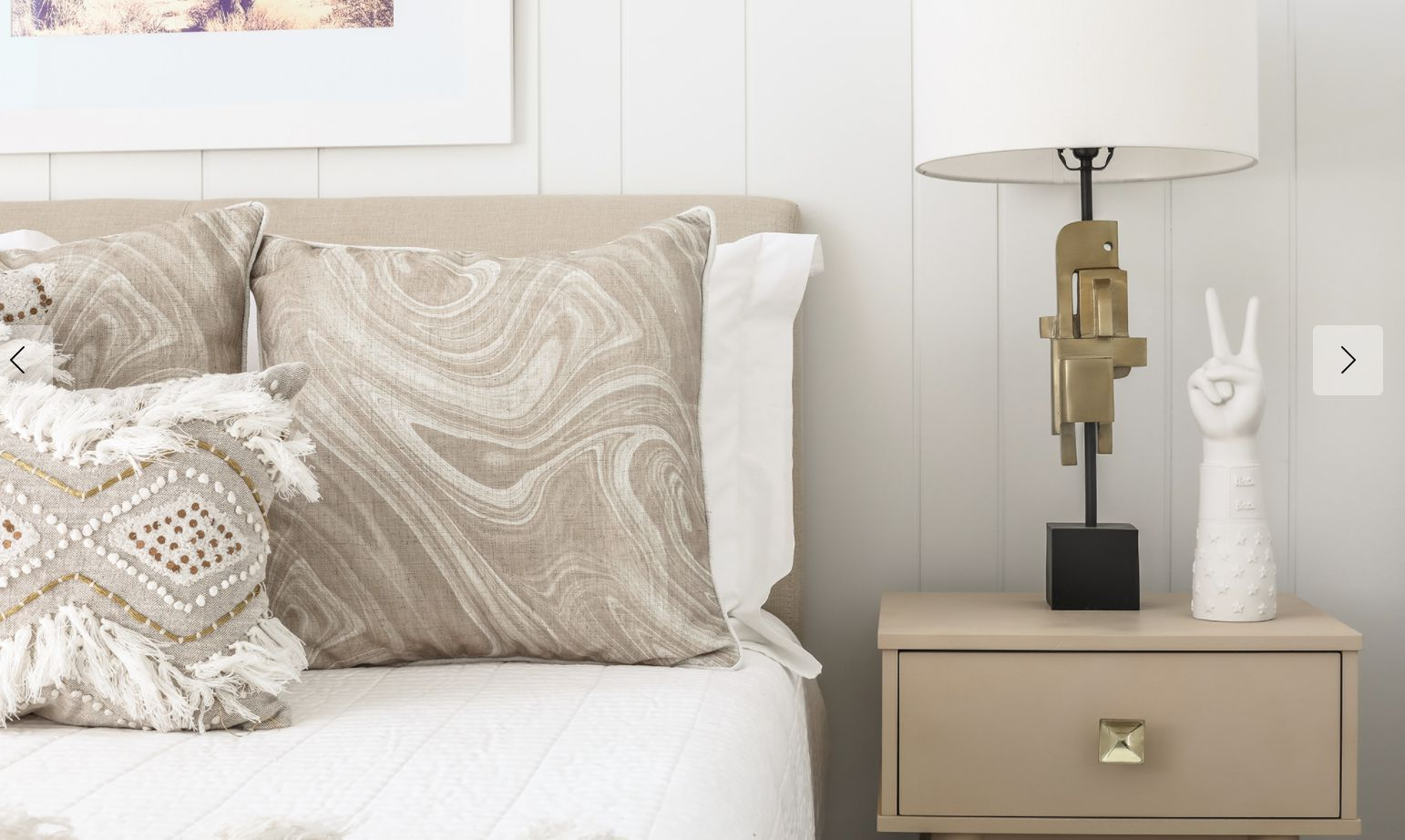 bedroom with white statue of hand making peace sign and abstract base of lamp