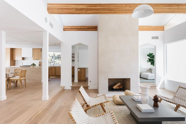 Living room with textured fireplace, wooden beams and white wood furniture