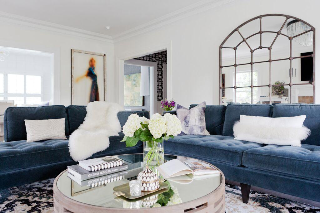Blue velvet sofa with metal mirror above.
