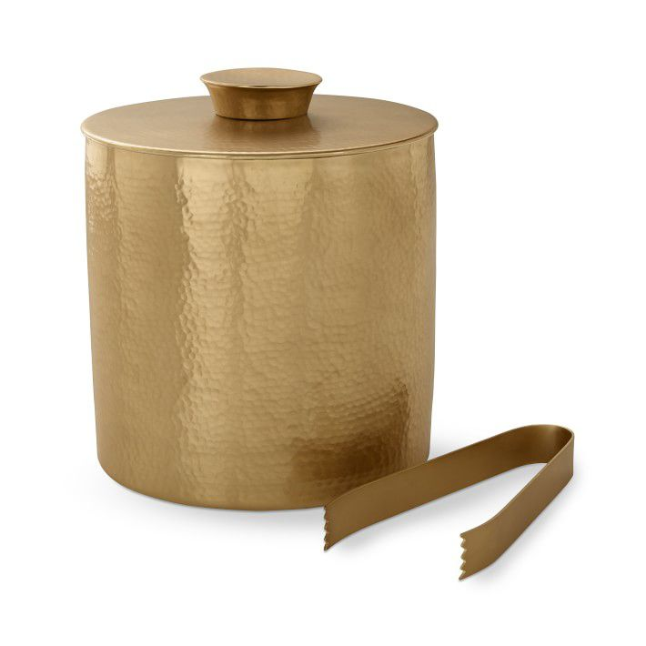 A hammered-copper ice bucket with matching tongs.
