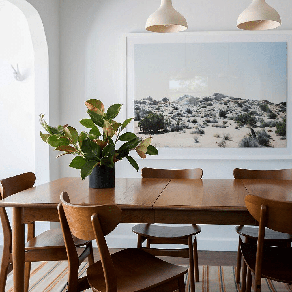 A dining room with mid-century modern furniture and sleek off-white pendant lights