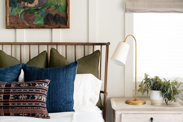 A bedroom with an olive and navy color palette