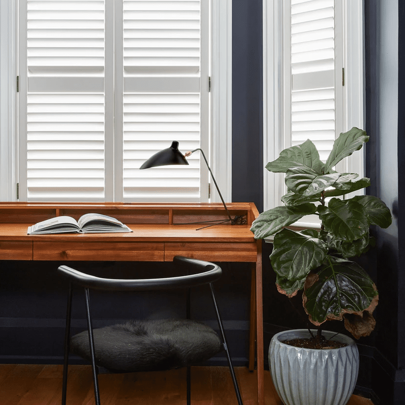 A home office with midcentury modern furniture and navy walls