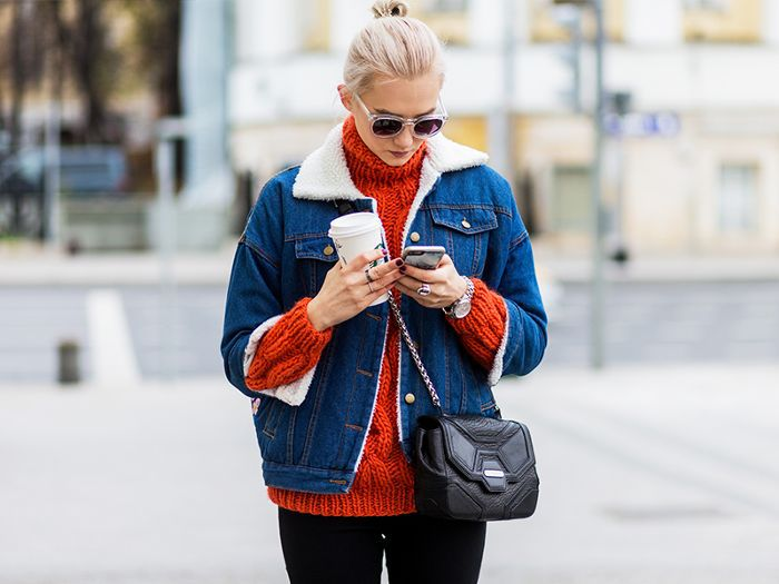a woman holding a coffee and looking at her phone and thinking about whether or not to make a purchase
