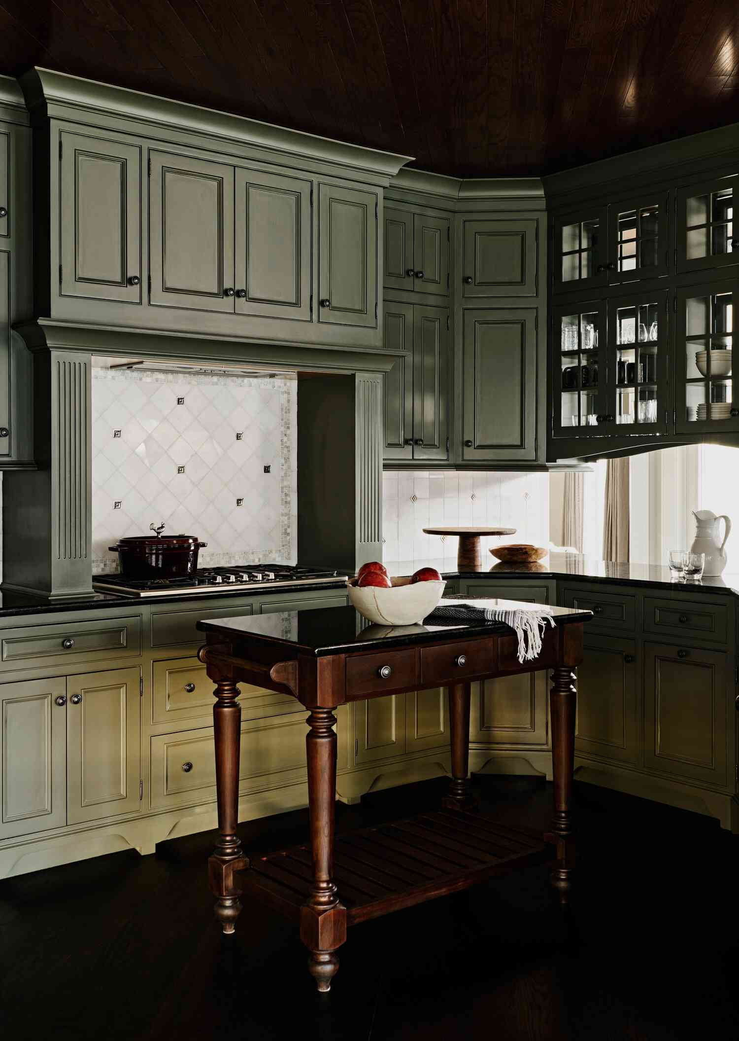 A kitchen with mint green cabinets and a white tiled backsplash, which has been framed by smaller gray tiles