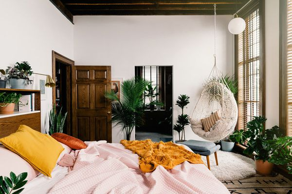 A Scandi-Boho bedroom with a messy bed, loads of plants, and a hanging seat.