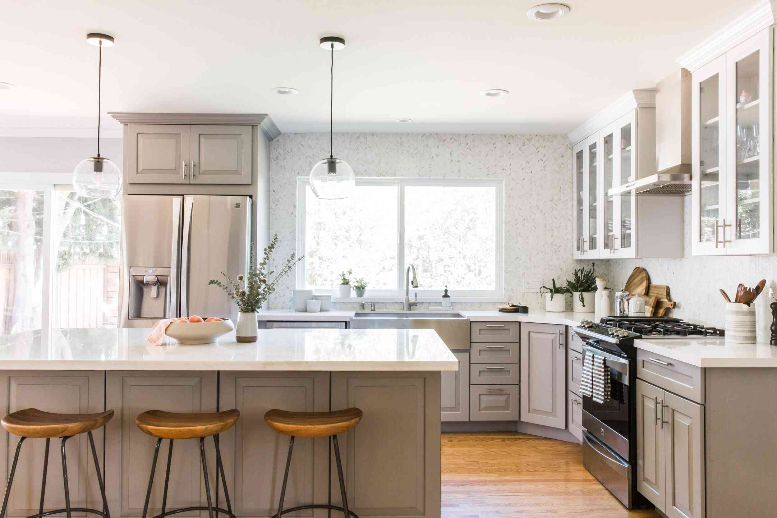 A kitchen with gray cabinets and a white tiled backsplash