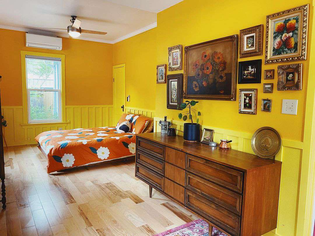 Bright yellow and orange bedroom with gallery wall