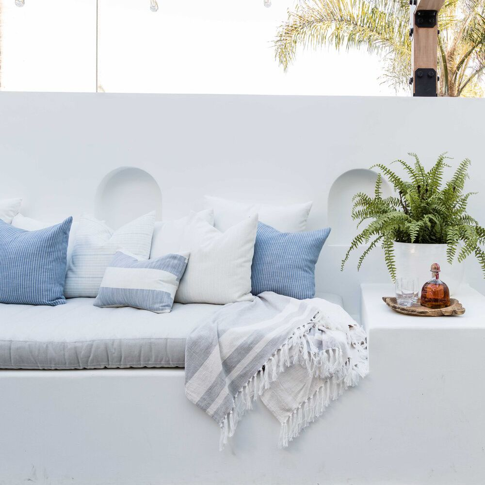 An outdoor deck with a sculptural white bench and several outdoor throw pillows